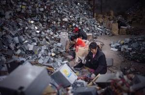 Women break apart hard drives in Guiyu near Guangdong, south China