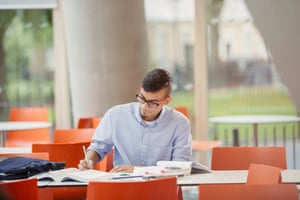 Male college student studying at tableStudents who are socialising at University