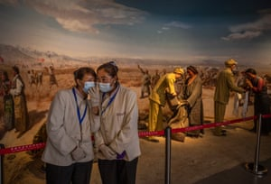 Tibetan workers chat in front of a display at the Tibet Million Serfs Memorial Hall in Lhasa