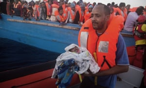A man carries his five-day-old son after been rescued during a Mediterranean crossing