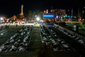 People sleep in a parking lot in Las Vegas on 30 March 2020 in a temporary shelter set up by Catholic Charities of southern Nevada after the organization's night shelter was forced to close temporarily due to Covid-19 infections