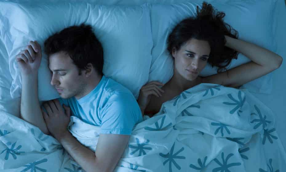 Couple lying together in bed, with the man asleep while the woman lies awake