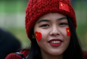 A supporter of China's President Xi Jinping waits on the Mall for him to pass during his ceremonial welcome, in London