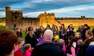 A tour guide with visitors on a Harry Potter theme tour of Alnwick Castle in Northumberland.
