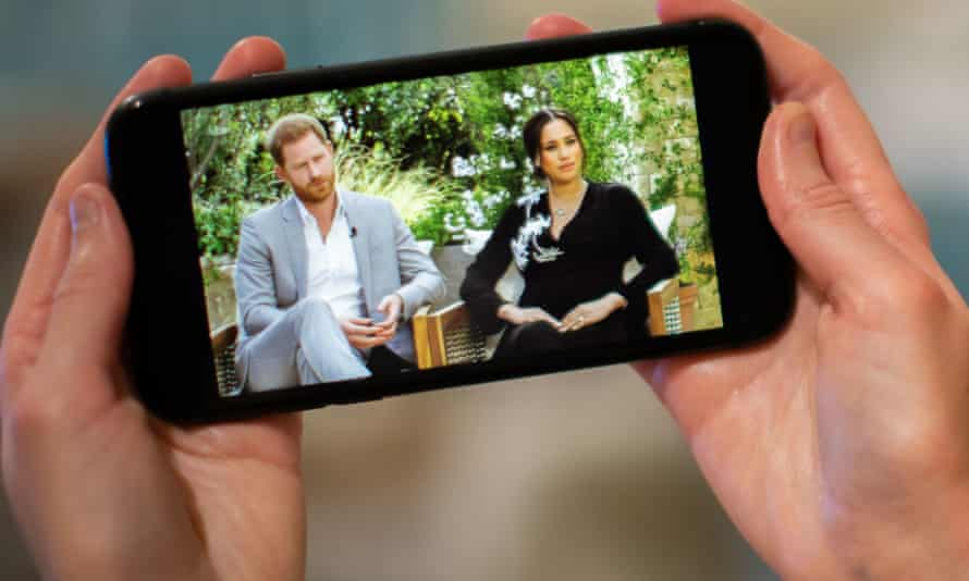 A man watches the Duke and Duchess of Sussex interview with Oprah Winfrey on a phone screen.