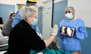 A Covid-19 patient uses a tablet to speak to a relative who is unable to visit, in Milan, Italy.