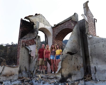 Steve Zielinski, Elizabeth Barkley and daughters Brooke and Delaney stand in the remains of their home.
