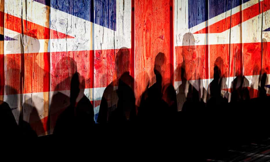 Row of people's shadows against backdrop of Union flag