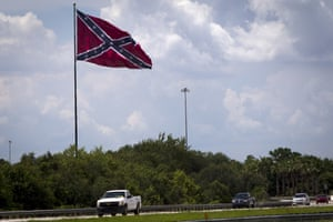 Large Confederate flag flying alongside a highway in Tampa with cars driving by.