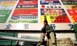 A worker rests in front of a billboard which promotes Chinese brands in Beijing.