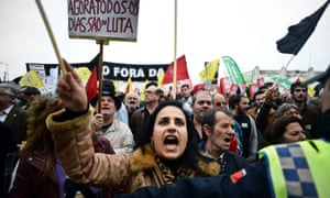 A woman shouts slogans as she protests with thousands of demonstrators against the austerity measures of the Portuguese government in 2013.