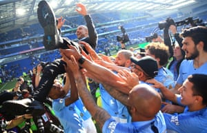 May 12: Manchester City players throw Pep Guardiola in the air as they celebrate winning the Premier League.