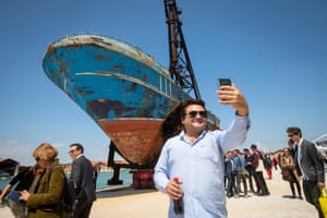 A man takes a selfie in front of Barca Nostra, the remains of a fishing vessel that sank whilst carrying migrants from Libya in 2015.