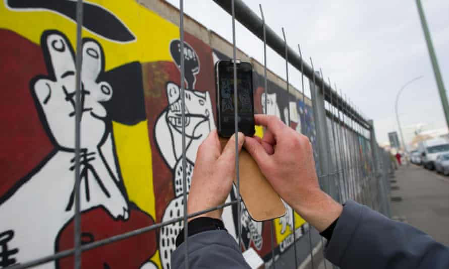 A tourist takes a picture at the East Side Gallery.