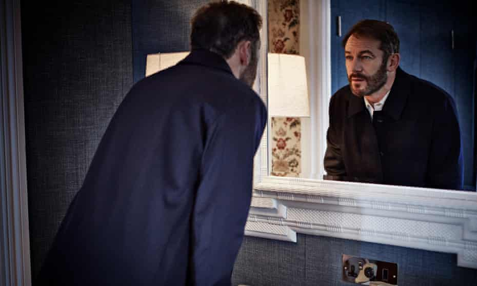 Jason Isaacs leaning towards a mirror – and his reflection