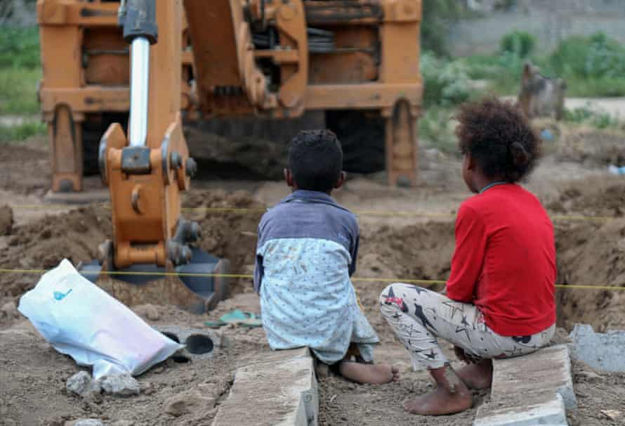 Yemeni children watch as an excavator digs graves at a specific plot for Covid-19 victims, at a cemetery in Taez, on 14 June 2020.