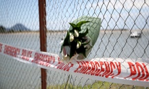 Floral tributes are placed on a fence at the Whakatane Wharf after the White Island eruption