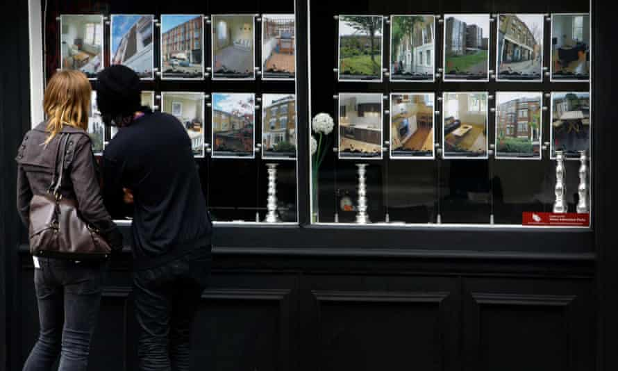 Young people look at details of properties in an Estate agents window