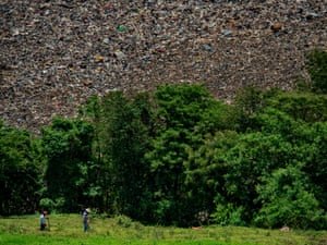 A waste truck on its way the Nejapa waste dumping area which is close to the Joya Galana community on the bottom of the hill men placing seeds to harvest corn right next tot the dump which contaminates the areas around the community as well as a strong smell in the ares which affects the residents health and way of living.