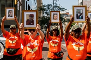 Mothers of murdered children hold pictures of their deceased children, seeking to end violent crime in Columbus, US