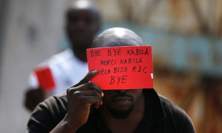 An opposition supporter displays a red card against President Joseph Kabila's rule.