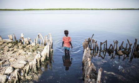 A young girl stands outside her home where her family's kitchen was swallowed up by the sea on Diamniadio Island in Senegal's Saloum Delta.