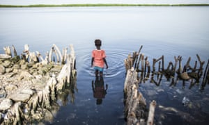 A young girl wades into water where the family kitchen once stood in Diamniadio Island, Saloum Delta in Senegal