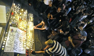 People light candles by a sign that reads 'Europe: your hand is covered with blood' at Keleti station in Budapest during a vigil for the 71 migrants who suffocated to death in an abandoned truck in Austria.
