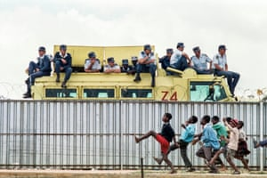 The photograph by Graeme Williams taken in Tokoza Township, Johannesburg, in 1991. Police watch an ANC rally while children taunt them.