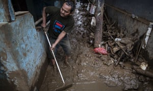 A man cleans mud from his Jakarta home
