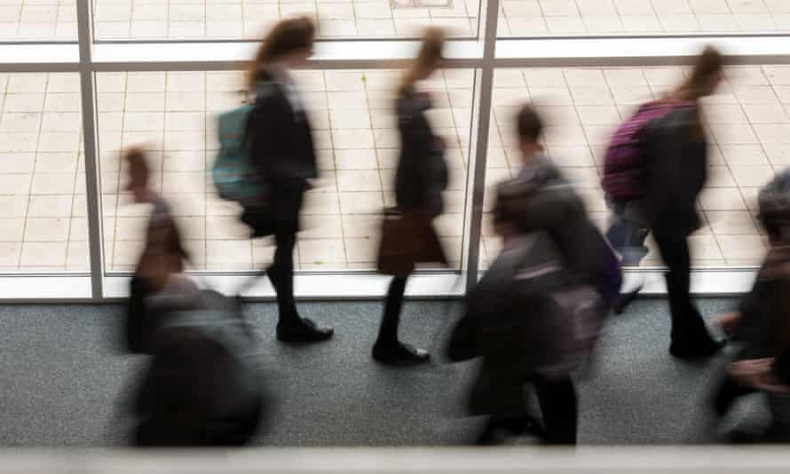 Secondary school pupils moving by a window in a school UK, blurred movement