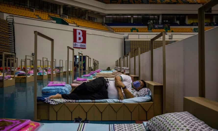 A Bangkok metropolitan administration employee tests out a cardboard bed at a field hospital for Covid-19 patients in Bangkok.