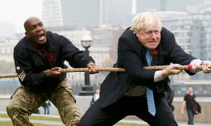 Boris Johnson taking part in a tug of war with members of the armed services to launch the London Poppy Day, outside City Hall this morning