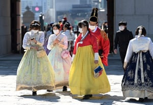 People in traditional Korean hanbok dresses wear face masks as they visit Gyeongbokgung palace
