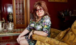 Patrizia Reggiani perched on an armchair wearing a short, colourful dress and sunglasses