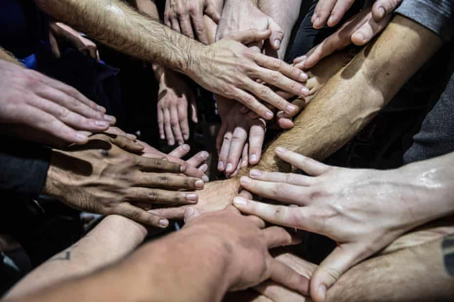 At the end of the Wimp to Warrior training session, everyone puts their hands together in a team building exercise.