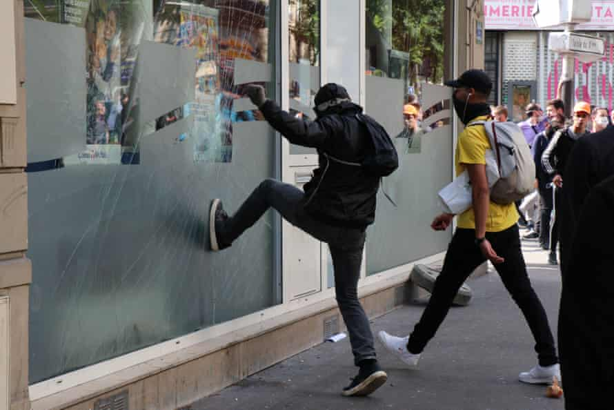 A protesters tries to kick in the window of a shop in Paris.
