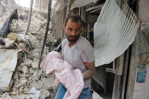 A man carries the body of an infant retrieved from under the rubble of a building following a reported airstrike on the al-Muasalat area