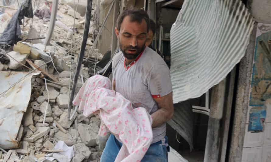 A Syrian man carries the body of an infant retrieved from under the rubble of a building following a reported airstrike on the al-Muasalat area of Aleppo.