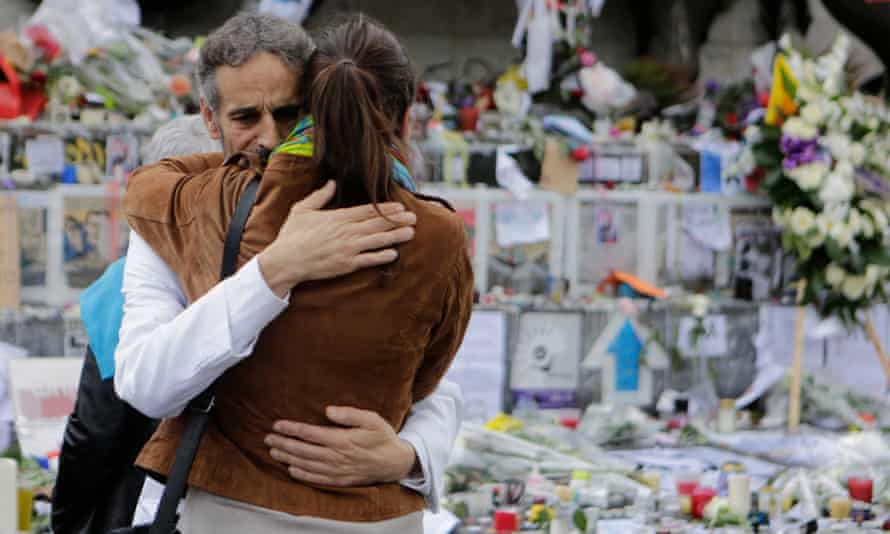 A city in mourning: two people comfort each other at the memorial at the Place de la Republique