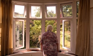 81 year old elderly woman looking out of her front room window