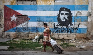 A woman walks by a mural with the Cuban flag and an image of revolutionary leader Che Guevara in Havana.