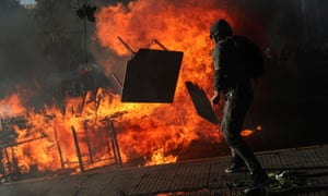 A demonstrator tosses furniture into an improvised bonfire during an anti-government protest in Santiago.