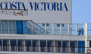 close up of the Costa Victoria cruise ship with two people wearing masks