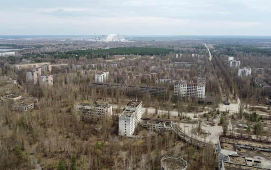 A new secure confinement structure atop the old sarcophagus that covers the damaged fourth reactor, with the abandoned city of Pripyat in the foreground.