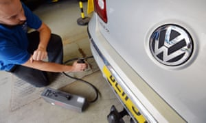A Volkswagen Passat car is tested for its exhaust emissions by a mechanic at an MOT testing station in Walthamstow, London