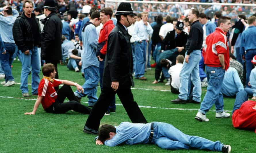 Injured fans lying on the pitch.