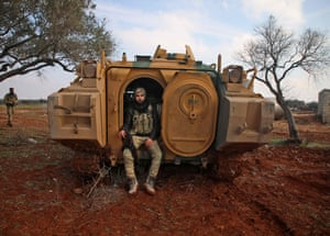 A Turkish-backed Syrian fighter sits in the back of an armoured personnel carrier as fighters assemble in the village of Miznaz on the western outskirts of Aleppo.