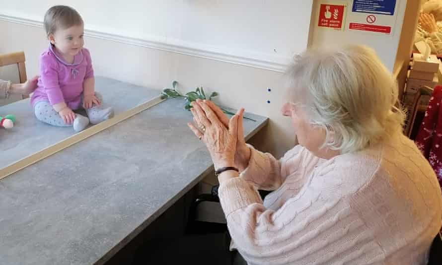 Margot Lawson meets her great-granddaughter, Cecilie, for the first time behind a glass partition in her care home in Surbiton, London, last week.
