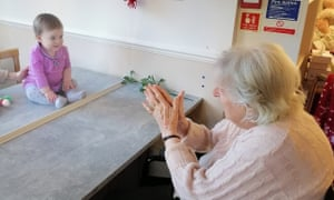 Margot Lawson meets her great-granddaughter, Cecilie, for the first time behind a glass partition in her care home in Surbiton, London, last week. Photograph: CHD Living/PA